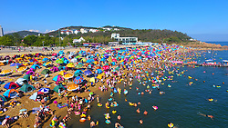 Aug. 8, 2017 - Dalian, China - Tourists and beachgoers with colorful sunshades, blanket the Fujiazhuang beach of Dalian, on the yellow sea coast of Liaoning Province. The beach attracts about 40,000 tourists each day in summer. (Credit Image: © Lyu Wenzheng/Xinhua via ZUMA Wire)