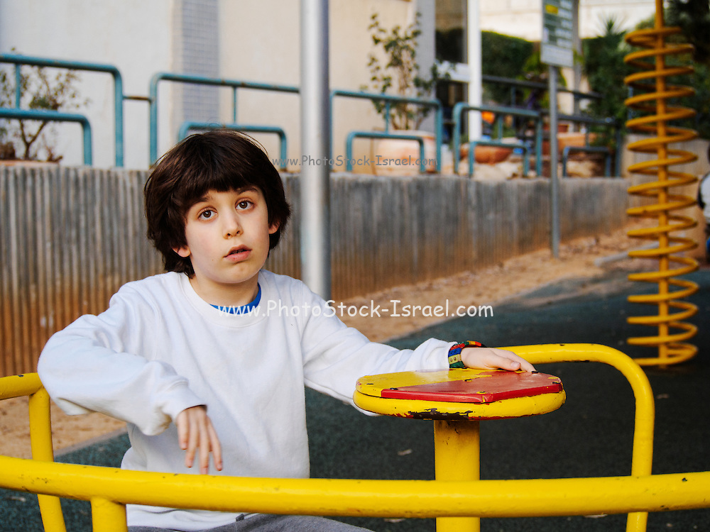 Young, elementary age boy playing outdoors ion a playground