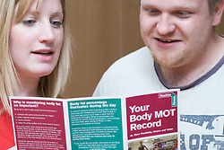 Fitness instructor going through a body MOT leaflet with a member at his sports leisure centre,