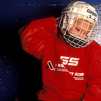 Canada, Saskatchewan, Young boy suits up for ice hockey practice in town of Melville on Saturday morning