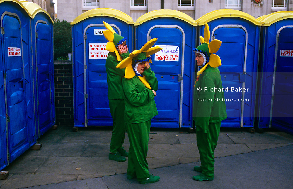 Three participants of the Lord Mayor's Show in the City of London await a free portaloo cublicle.