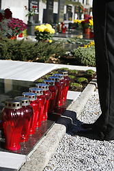 Candles on  a grave, woman standing at it.  (Photo by: Vid Ponikvar / Sportal Images).