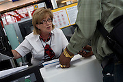 Mature lady employee shows passenger where departures gate is at British Airways check-in at Heathrow Airport's Terminal 5.