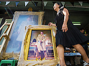 01 DECEMBER 2016 - BANGKOK, THAILAND: A woman wearing black mourning clothes walks past a portrait of HRH Crown Prince Maha Vajiralongkorn, who will soon be the new King of Thailand. Thailand's parliamentary body, the National Legislative Assembly, invited HRH Crown Prince Maha Vajiralongkorn to be king following the death of the Crown Prince's father, Bhumibol Adulyadej, the Late King of Thailand. The invitation marked the formal beginning of the process of naming the new King, although Crown Prince Vajiralongkorn was the heir apparent and Bhumibol's appointed successor. Shops that sell royal paraphernalia are now selling new portraits of  Crown Prince Vajiralongkorn which will be displayed alongside portraits of his late father. King Bhumipol died on Oct 13.      PHOTO BY JACK KURTZ