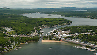 As the clouds clear on Saturday a steady flow of traffic begins to arrive for the beginning of Laconia's Motorcycle Week as seen from Lakes Biplane looking down on Weirs Boulevard.  (Karen Bobotas/for the Laconia Daily Sun)