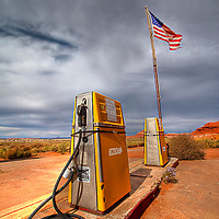 A tattered United States Flag fluttering above antique gas pumps under a cloudy sky near Capitol Reef National Park, Utah portends two possible futures.  The first, is free of fossil fuels where petrol stations such as these are obsolete.  The alternate is one in which the United States is left fighting to sustain its oil addiction and against the ravages of fossil fuel induced global warming.