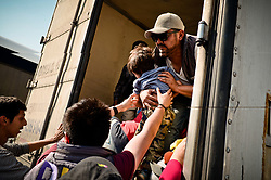November 10, 2018 - Tepotzotlan, Mexico - A man lifts a child into a semi-truck trailer as other form the caravan of Central American migrants board trailers on the Mexico-Queretaro highway, in the municipality of Tepotzotlan. (Credit Image: © Omar LopezZUMA Wire)