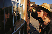 Route 395: Eastern Sierra Nevada Mountains of California. Ghost Town, Bodie, California - now a state historic park. Faith D'Aluisio looks in the window. MODEL RELEASED.