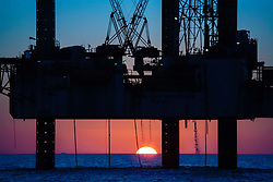 Offshore drilling rig Oil and gas jackup offshore drilling rig with a colorful sunset in the Gulf of Mexico.