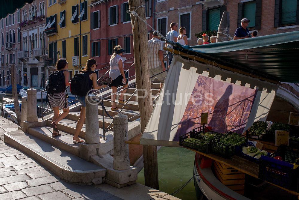 Pedestrians and tourists walk over a canal bridge with shadows on an afternoon sun screen in Dorsoduro, a district of Venice, Italy. The minor bridge spans the canal where various barges and boats ply various trades including this seller of fruit and veg at more reasonable prices than the hundreds of cafes and restaurants. As the visitors climb the steep steps, they leave their shadows on a screen there to shade the produce from hot afternoon sunshine. Waterways are used heavily for deliveries of supplies, goods being sold and consumed before the influx of tourists who, in their own way, flood the narrow streets and smaller canals with gondolas.