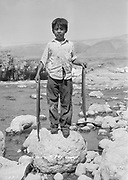 9305-B7332. Roger Jim Sr. (1931-1988) as a young boy stands on rock posing with two large eels (Pacific lamprey). Celilo Falls in background.