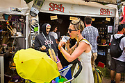 Glastonbury Festival, 2015.<br /> Mother eating ice cream while pushing her pram in front of tribal wear stall.
