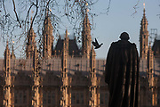 The monument to Benjamin Disraeli, Earl of Beaconsfield with the British Houses of Parliament in the background, on 18th January 2017, in Parliament Square, London England. The statue of Benjamin Disraeli is an outdoor bronze sculpture by Mario Raggi, located at Parliament Square in London, United Kingdom. Installed in 1883, it features a bronze statue on a red granite plinth. The memorial is located at the west side of the square, facing the Houses of Parliament, and is Grade II-listed.
