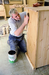 Man with learning disability waxing chest of drawers,