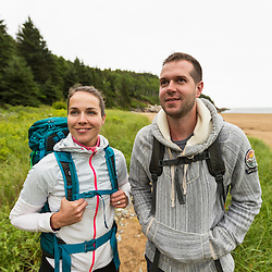 A couple hiking on a cloudy morning at Sand Beach in Maine's Acadia National Park.