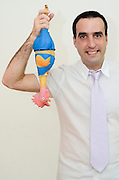 Young Man in his thirties with button down shirt and tie holds a plastic chicken