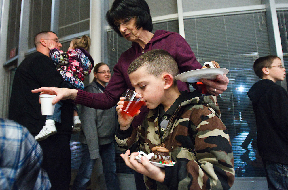 Cooper Grim, 7, of Grand Island takes a sip of punch after getting a cupcake and some candy with grandma Maureen Adams before the lighting of the community Christmas tree Tuesday at City Hall. (Independent/Matt Dixon)