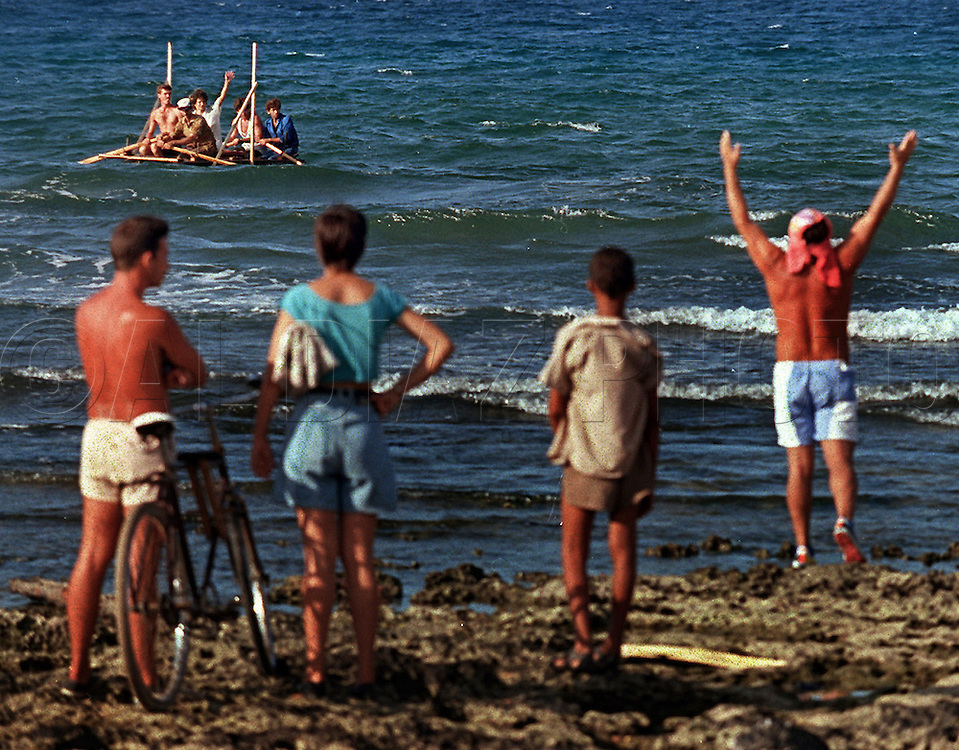 8/1994-Al Diaz/Miami Herald--In 1994 Cuban balseros turned the tiny fishing village of Cojimar into a major point of embarkation for thousands seeking a better life. Here, Cuban rafters depart the coast of Cojimar as spectators watch from the rocky shoreline.