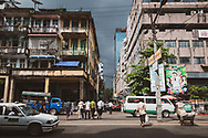 Yangon, Myanmar - October 22, 2011: Street scene with pedestrians, street traffic, and weathered buildings in Burma's largest city.