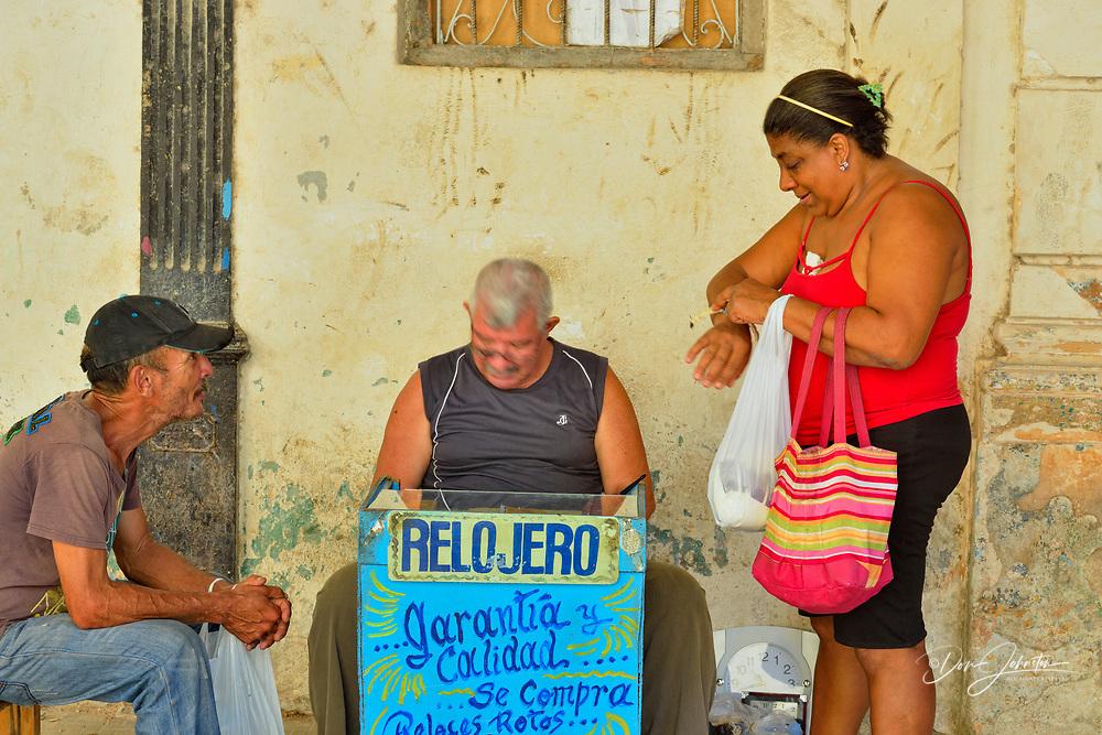 Street commerce in Old Havana- A watch repairman and his patrons, La Habana (Havana), Habana, Cuba