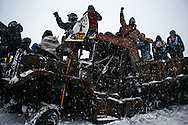 Protestors stand on an abandoned and burned vehicle on Highway 1806 during an action against the Dakota Access Pipeline in Cannon Ball, North Dakota in December 2016.<br /> <br /> The protest camps located on US Army Corps land are located on a floodplain of the Cannonball and Missouri rivers. Concerns of flooding and resulting environmental damage from structures and waste at the camps have prompted evacuations and evictions ordered by both the Army Corps of Engineers and the Tribal Council.
