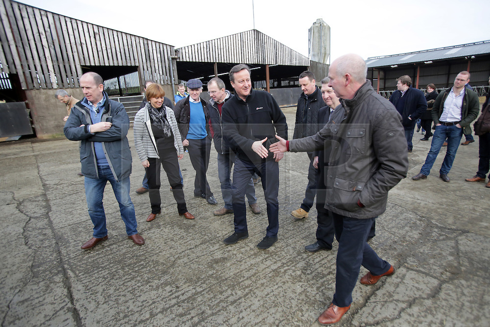 Licensed to London News Pictures. 27/02/2016. Ahoghill, County Antrim, Northern Ireland, UK. Prime Minister David Cameron greets farmers during a tour of Harry Johnston dairy farm in Ahoghill, County Antrim. The Prime Minister was on a tour to persuade voters that membership of a reformed EU is in their best interests. Photo credit : Paul McErlane/LNP