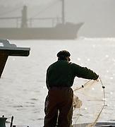 A fisherman sorting his nets near the Galata Bridge at the Bosphorus, Istanbul, Turkey