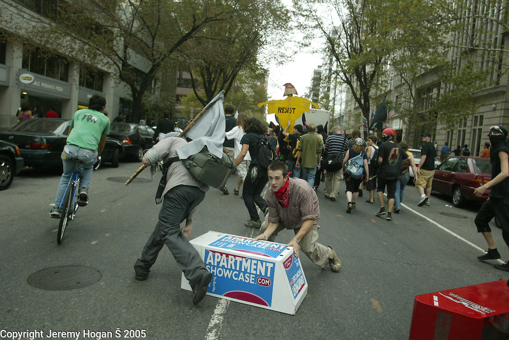 Black Bloc Anarchists toss newspaper stands into a street hoping to stall police who are in pursuit during the anti-war march on Washington.