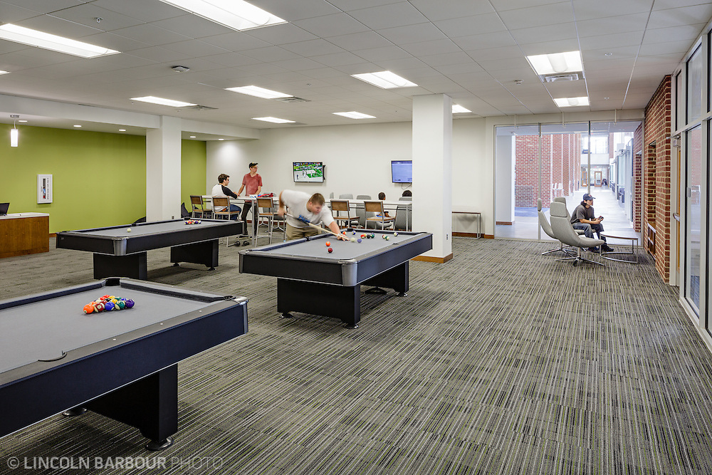 An activity space inside of the Liberty Student Center with multiple televisions and pool tables.