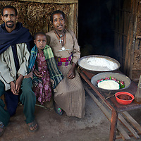 "Wubalem, her husband Tsega and daughter Rekebki with a weeks supply of food outside their home. The food includes vegetables, maize and sorghum flours, vegetable oil and a paste of spices. <br /> <br /> Wubalem Shiferaw, age 23, lives in the village of Mecha with her husband Tsega Bekele, age 33, and their daughter Rekebki, age 4. Wubalem remembers her grandparents harvesting honey. She has maintained this tradition while moving to modern hives which produce a far greater yield of honey. Wubalem is a member of the Mecha village Cooperative which brings together local women beekeepers allowing them to share insights and build a credit union. The Mecha village Cooperative is not yet a member of the Zembaba Union. Wubalem's husband Tsega is a priest and a tailor. <br /> <br /> Harvesting honey supplements the income of small farmers in the Ethiopian region of Amhara where there is a long tradition of honey production. However, without the resources to properly invest in production and the continued use of of traditional, low-yielding hives, farmers have not been able to reap proper reward for their labour. <br /> <br /> The formation of the Zembaba Bee Products Development and Marketing Cooperative Union is an attempt to realize the potential of honey production in Amhara and ensure that the benefits reach small producers. <br /> <br /> By providing modern, high-yield hives, protective equipment and training to beekeepers, the Cooperative Union helps increase production and secure a steady supply of honey for which there is growing demand both in and beyond Ethiopia. The collective processing, marketing and distribution of Zembaba's ""Amar"" honey means that profits stay within the cooperative network of 3,500 beekeepers rather than being passed onto brokers and agents. The Union has signed an agreement with the multinational Ambrosia group to supply honey to the export market. <br /> <br /> Zembaba Bee Products Development and Marketing Cooperative Union also provides credit to individual members and trains carpenters in the pro"