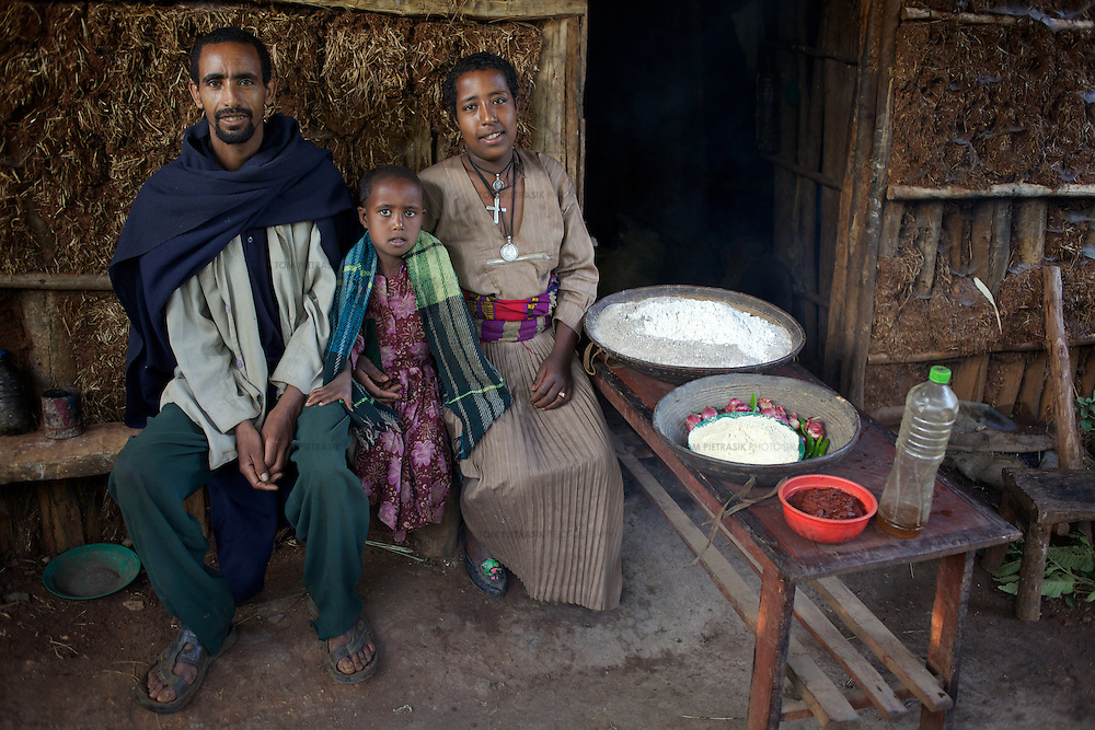 """Wubalem, her husband Tsega and daughter Rekebki with a weeks supply of food outside their home. The food includes vegetables, maize and sorghum flours, vegetable oil and a paste of spices. <br /> <br /> Wubalem Shiferaw, age 23, lives in the village of Mecha with her husband Tsega Bekele, age 33, and their daughter Rekebki, age 4. Wubalem remembers her grandparents harvesting honey. She has maintained this tradition while moving to modern hives which produce a far greater yield of honey. Wubalem is a member of the Mecha village Cooperative which brings together local women beekeepers allowing them to share insights and build a credit union. The Mecha village Cooperative is not yet a member of the Zembaba Union. Wubalem's husband Tsega is a priest and a tailor. <br /> <br /> Harvesting honey supplements the income of small farmers in the Ethiopian region of Amhara where there is a long tradition of honey production. However, without the resources to properly invest in production and the continued use of of traditional, low-yielding hives, farmers have not been able to reap proper reward for their labour. <br /> <br /> The formation of the Zembaba Bee Products Development and Marketing Cooperative Union is an attempt to realize the potential of honey production in Amhara and ensure that the benefits reach small producers. <br /> <br /> By providing modern, high-yield hives, protective equipment and training to beekeepers, the Cooperative Union helps increase production and secure a steady supply of honey for which there is growing demand both in and beyond Ethiopia. The collective processing, marketing and distribution of Zembaba's """"Amar"""" honey means that profits stay within the cooperative network of 3,500 beekeepers rather than being passed onto brokers and agents. The Union has signed an agreement with the multinational Ambrosia group to supply honey to the export market. <br /> <br /> Zembaba Bee Products Development and Marketing Cooperative Union also provides c"""