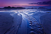 Tidal water flows back to the sea out a channel on the beach at Seal Rocks, Oregon
