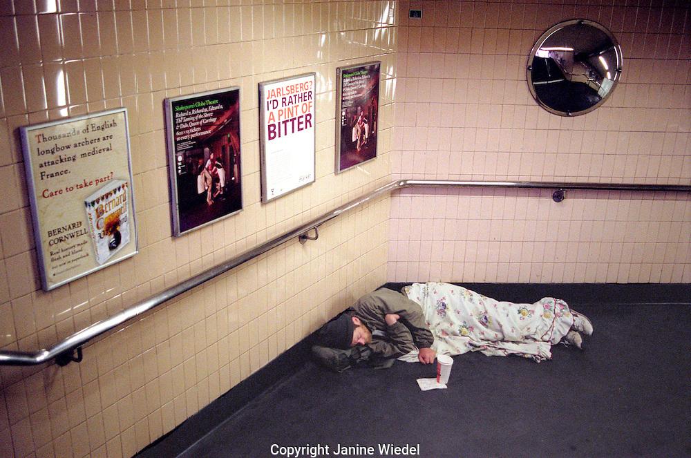 Homeless person asleep in London underground.