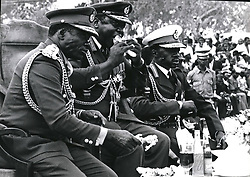 Dec. 12, 1965 - Koboko. Uganda : During the celebrations of 7th anniversary of his military coup, life president al-hajji dr. idi amin Dada, vc, dso, mc, conqueror of the British and commander-in-chief of the armed forces takos a bito at roasted chicken-leg while watching the military parade. on his right is his vice president, general mustafa adrsi, who is also minister for defance. (Credit Image: © Keystone Pictures USA/ZUMAPRESS.com)