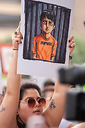 Diana Rubio who is a DACA young person, holds an illustration by artist Kalyn Duke to protest the Trump adminstration's policy of separating familes at the border during the Familes Belong Together rally, part of a nationwide protest demanding that the policy stop.