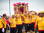 """23 JUNE 2015 - MAHACHAI, SAMUT SAKHON, THAILAND: Men carry the City Pillar Shrine to the Tha Chin (Chin River) during the procession for the shrine in Mahachai. The Chaopho Lak Mueang Procession (City Pillar Shrine Procession) is a religious festival that takes place in June in front of city hall in Mahachai. The """"Chaopho Lak Mueang"""" is  placed on a fishing boat and taken across the Tha Chin River from Talat Maha Chai to Tha Chalom in the area of Wat Suwannaram and then paraded through the community before returning to the temple in Mahachai.   PHOTO BY JACK KURTZ"""