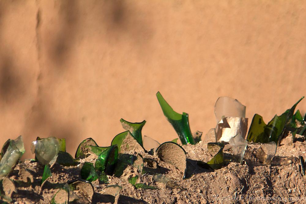 Africa, Morocco, Skoura. Broken glass bottles on kasbah walls.