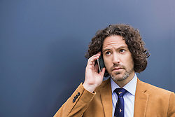 Young handsome businessman long hair cell phone
