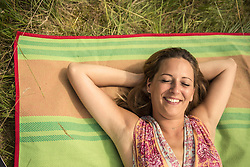 Directly above shot of woman resting on picnic blanket on meadow and smiling, Bavaria, Germany