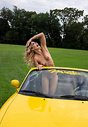Happy nude woman posing in a yellow Miata with the top down in the middle of a green meadow