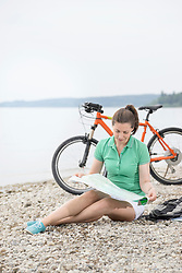 Mature woman with electric bike by lake looking at road map, Bavaria, Germany