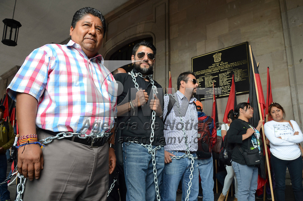 Toluca, México.- Encadenados y con banderas rojinegras, cerca de 50 manifestantes pertenecientes a la UPTN (universidad del Pueblo Trabajador de Nezahualcoyotl) se manifestaron frente a palacio de gobierno exigiendo la reinstalacion en cumplienmto a la reforma educativa. Agencia MVT / Arturo Hernández.