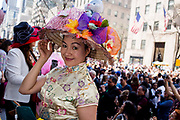 New York, NY - April 16, 2017. An Asian woman wearing an elaborate hat on the steps of St. Patrick's Cathedral at New York's annual Easter Bonnet Parade and Festival on Fifth Avenue.