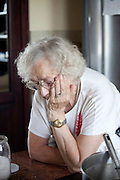 Polish great grandmother age 88 in her kitchen deep in thought. Zawady Central Poland