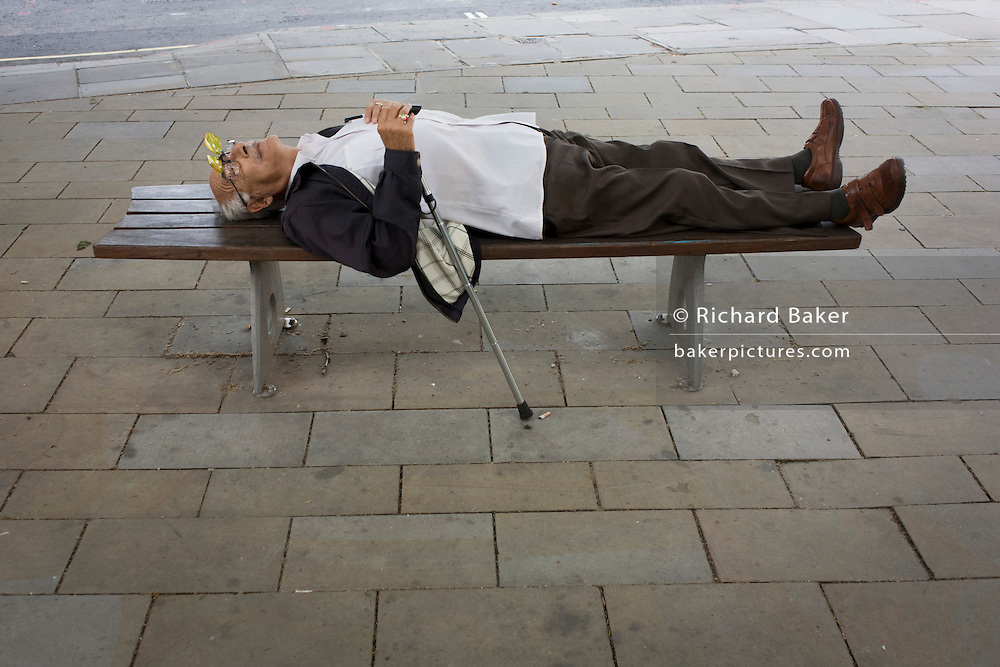 Guarding his walking stick, an elderly gentleman sleeps on a city street bench in central London.