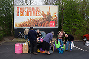 Locals sift through second-hand possessions below a Goodtimes ad during a Sunday car boot sale in a supermarket car park. Stalls have been set up at the rear of family cars and their contents are displayed for passers-by to browse and haggle for thrifty bargains. Car boot/trunk sales or boot/trunk fairs are a mainly British form of market in which private individuals come together to sell household and garden goods. The term refers to the selling of items from a car's boot or trunk.