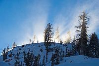 Sun illuminates the snow blown over a ridge at Alpine Meadows, Lake Tahoe, California