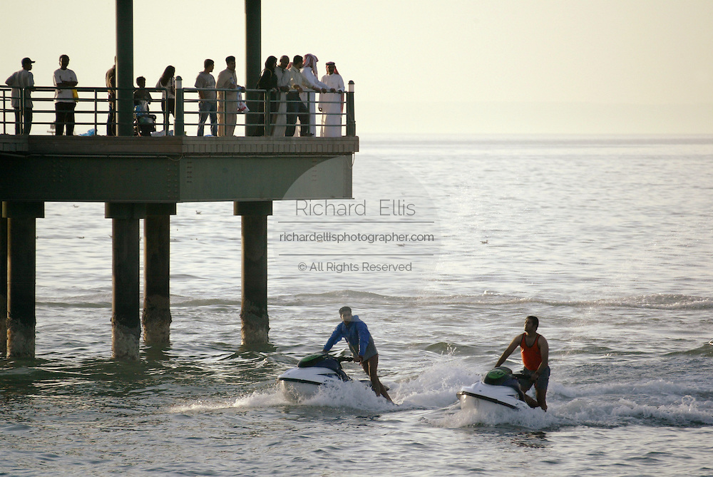 Kuwaiti's watch two young men on jet skis from the Sharq Pier in Kuwait City along the Persian Gulf.