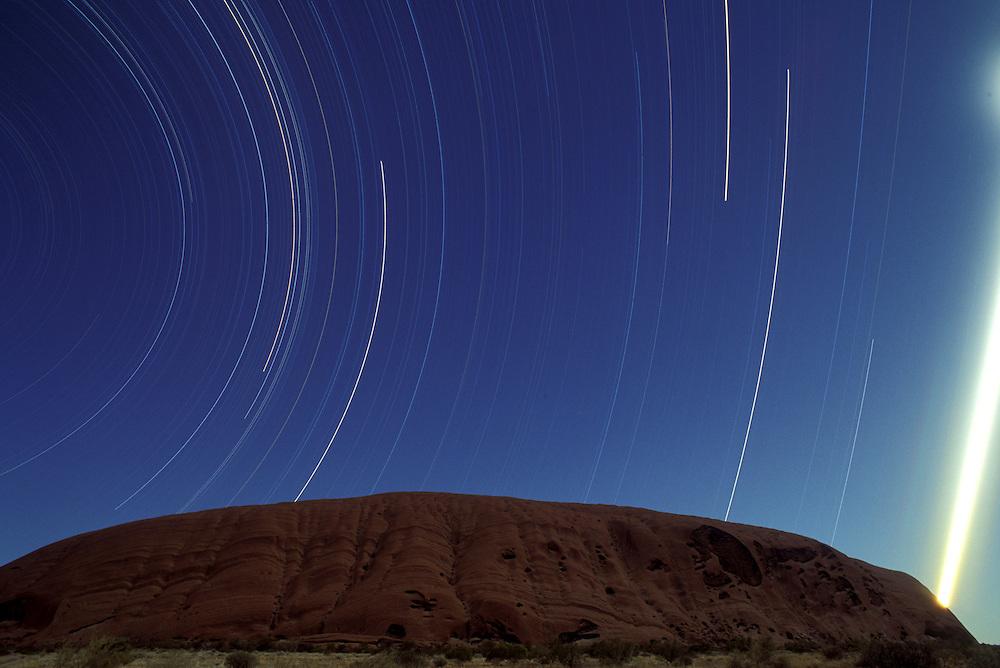 Australia, Northern Territory, Uluru - Kata Tjuta National Park, Stars circle above Ayers Rock during nighttime exposure