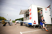 Enja from Latvia works at Put The Kettle On snack bar. The burger van is situated in the parking area of a Shell petrol station and Kiss Kiss adult supermarket on the 28th April 2010 in Guyhirn in the United Kingdom.